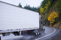 Semi truck and reefer trailer wheels in autumn rain dust. Spectacular powerful semi truck with a reefer trailer at the turn of the winding road passing among the stock photos