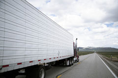 Semi truck rig with reefer driving on oncoming traffic line Royalty Free Stock Images