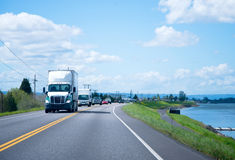 Semi truck on road ahead of column along the river Royalty Free Stock Photos