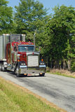 Semi truck on rural road. Red commercial semi truck on narrow rural street Stock Photo