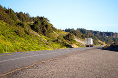 Semi truck with semi trailer move on beautiful highway with gree Stock Image