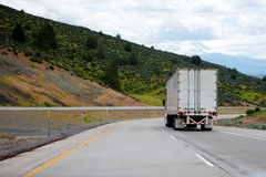 Semi truck with semi trailer move down on winding highway with g Stock Images