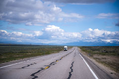 Semi truck staying out of road in Nevada. The view from the endless road endless plains, picturesque cloudy sky and a small semi truck standing on the roadside Stock Image