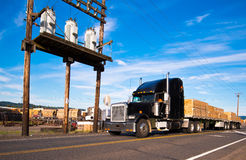 Semi Truck with timber near an electrical substation Royalty Free Stock Images
