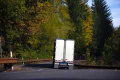 Semi truck trailer back view on winding autumn forest road Stock Image