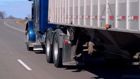 Semi truck and trailer driving on the freeway on a sunny day.