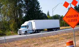 Semi truck trailer on highway and road sign Stock Photos