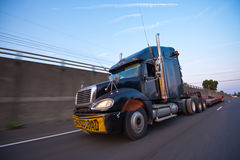 Semi Truck with trailer inscription overload at speed on highway. Powerful and effective modern black truck with chrome pipes and large size sign oversized load stock photo