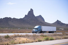 Semi truck and trailer on road with Arizona mountain. Fresh popular professional big rig semi truck with a reefer trailer moving on the divided highway on a Royalty Free Stock Photography