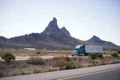 Semi truck and trailer on road of Arizona with mountain Royalty Free Stock Image