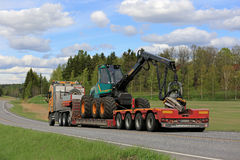 Semi Truck Transports Forestry Harvester at Spring Royalty Free Stock Photos