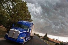 Semi Truck under heavy clouds Stock Photo