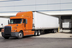 Semi truck by the warehouse. Orange semi truck by the door of warehouse Royalty Free Stock Images