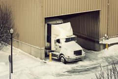 Semi truck and the warehouse seen winter time Royalty Free Stock Image