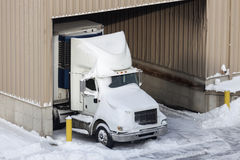 Semi truck and the warehouse seen winter time Royalty Free Stock Images
