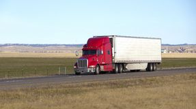 Semi truck with trailer. Semi truck with white trailer driving on snowy interstate highway stock photography