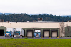 Semi trucks blue trailers loading unloading cargo in warehouse b Royalty Free Stock Images