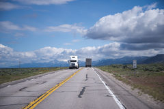 Semi trucks in both directions toward each other Stock Image