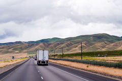 Semi trucks caravan going divided highway with silky Idaho mount Royalty Free Stock Image