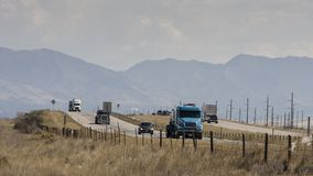 Highway traffic in Utah. Semi-trucks and cars driving on a highway in fron of mountains near Salt Lake City, Utah Stock Photography