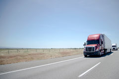 Semi trucks convoy on straight highway on flat plateau Stock Photography