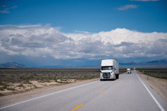 Semi trucks convoy on straight road in Nevada prairie Stock Photos