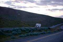 Semi trucks going uphill with light on evening Oregon highway Stock Photo