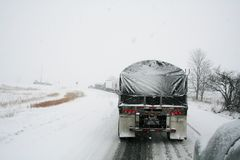 Semi trucks slowly trudge down the highway. Poor road conditions tend to cause unexpected congestion Royalty Free Stock Image