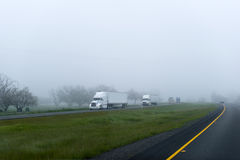 Semi trucks trailers big rigs cargo convoy on foggy highway. The convoy of big rig semi trucks and trailers in different colors on the highway with a dividing royalty free stock photos