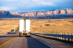 Semi trucks with trailers carrying cargo on the highway. Semi trucks with dry van and flat bed trailers carrying cargo on the highway with security fencing in Royalty Free Stock Image