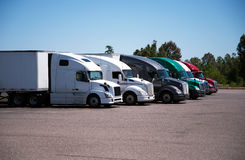 Semi-trucks and trailers of different make and models stand in r. Colorful modern big rigs Semi-trucks and trailers of different makes and models stand in row on Stock Photography