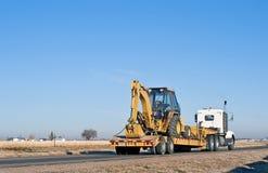 Semi-vrachtwagen die een back-hoe ladercombinatie vervoert Royalty-vrije Stock Afbeeldingen