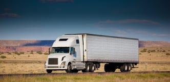 Semi-vrachtwagen op de weg in de woestijn Royalty-vrije Stock Foto