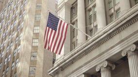 Semi zijschot die van Amerikaanse vlag in een kalme wind van een historisch financieel gebouw op Wall Street in Lager golven stock video