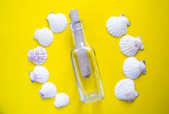 Semicircle of white seashells with message in a bottle on yellow background royalty free stock photo