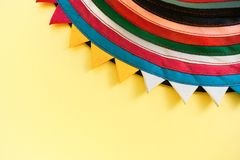 Semicircular handmade cloth of stitched from colorful stripes on top of bright pastel yellow background with copy space. Part of circle handmade striped Royalty Free Stock Photos