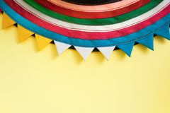 Semicircular handmade cloth stitched from colorful stripes on top of bright pastel yellow background. Royalty Free Stock Image