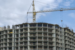 Semicircular monolithic house under construction. And tower crane against the blue sky Royalty Free Stock Photo