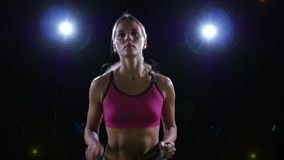Semicircular shooting from left to right running good looking girl backlit on black background. Slow motion. Close up. Semicircular shooting from left to right stock footage