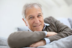 Semiling senior man on sofa Stock Images