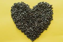 Semilla de girasol orgánica en forma del corazón En fondo amarillo Primer, visi?n superior fotos de archivo