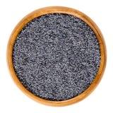 Semillas de amapola azul en cuenco de madera sobre blanco Foto de archivo libre de regalías