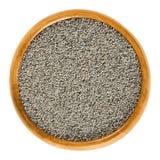 Semillas de amapola grises en cuenco de madera sobre blanco Foto de archivo