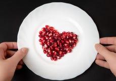 Semillas de la granada en la placa blanca Dimensión de una variable del corazón fotos de archivo libres de regalías