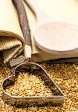 Semillas de lino de oro con el libro de cocina y el corazón Imagen de archivo libre de regalías