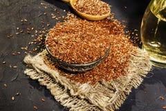 Semillas de lino en un cuenco de la arcilla y un aceite de linaza en un tarro de cristal en una tabla de madera El aceite de lina foto de archivo libre de regalías