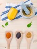Semillas de mostaza secadas negras y amarillas con el polvo de la cúrcuma en el wo Imagenes de archivo