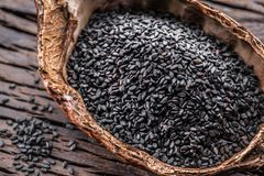 Semillas de sésamo negras en el cuenco orgánico en la tabla de madera vieja Visión superior imágenes de archivo libres de regalías