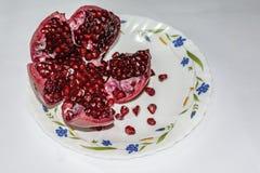 Semillas jugosas rojas peladas de la granada en la placa de cerámica con el fondo blanco imagen de archivo