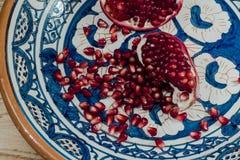 Semillas maduras y frescas de la granada en la placa tradicional hermosa de la arcilla de Oriente Medio Foto de archivo